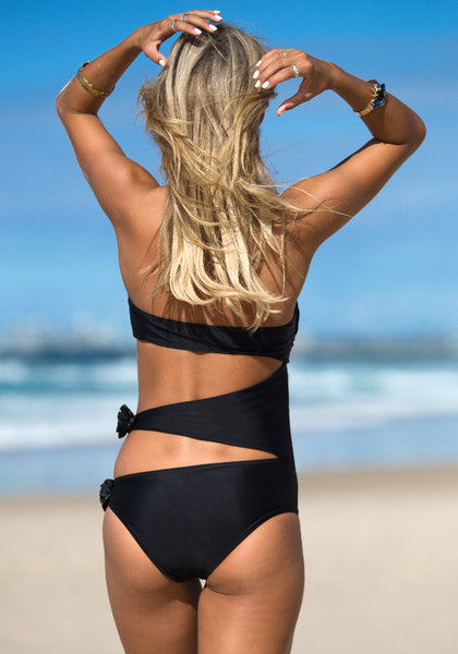 Back view of model in black cutout bandeau swimming suit