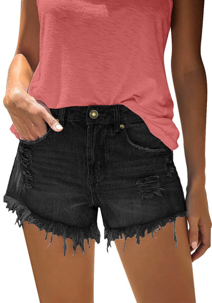 Model poses wearing black frayed raw hem ripped denim shorts