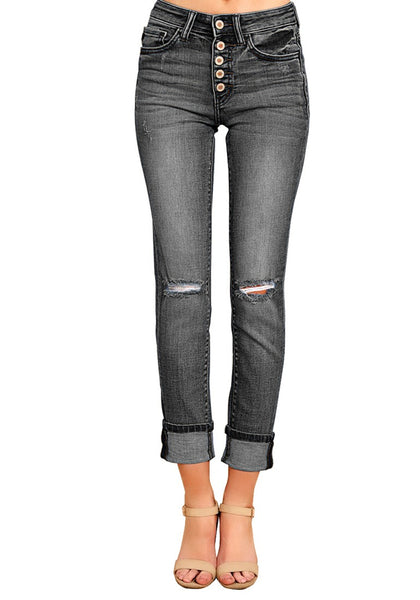 Front view of model wearing black rolled hem button-up ripped denim jeans