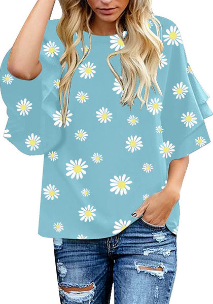 Front view of model wearing light blue trumpet sleeves keyhole-back daisy printed blouse