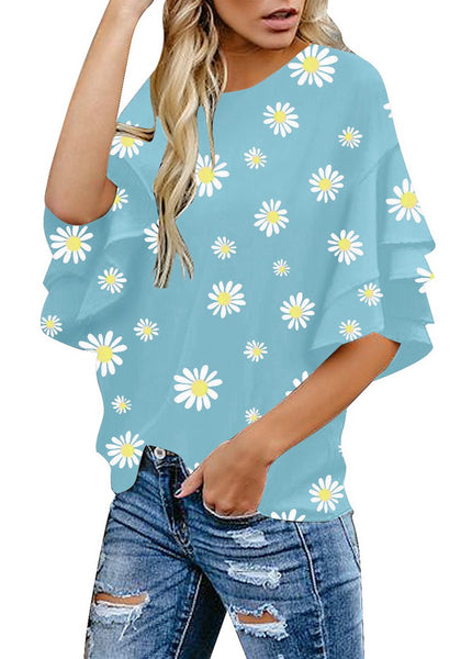 Angled shot of model wearing light blue trumpet sleeves keyhole-back daisy printed blouse