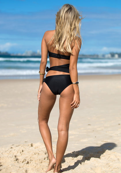 Full body back view of model in black cutout bandeau swimming suit