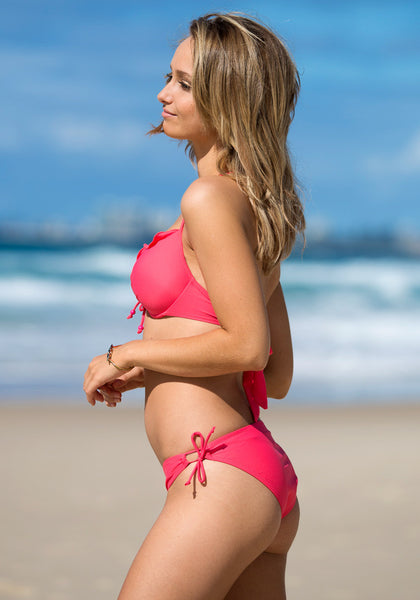 Side view of model in ruffles tie up bikini set - coral