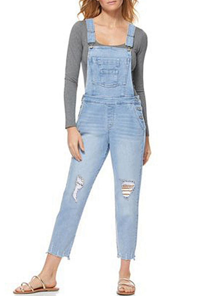 Model poses wearing light blue raw hem distressed cropped denim overalls