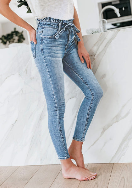 Model poses wearing light blue high-waist acid wash belted denim skinny jeans