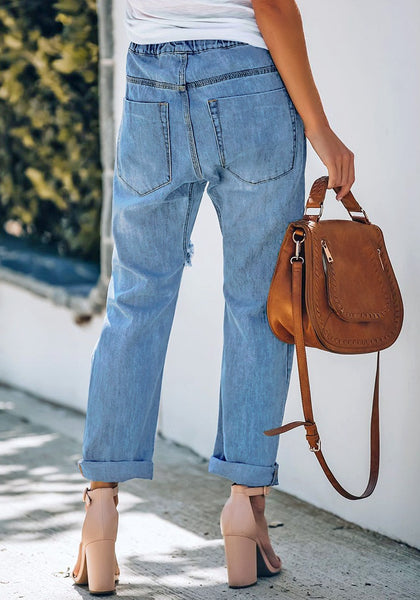 Back view of model wearing medium blue drawstring-waist cuffed raw hem ripped boyfriend jeans