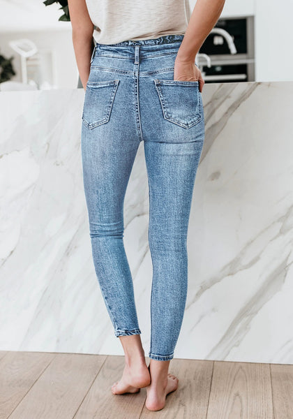 Back view of model wearing light blue high-waist acid wash belted denim skinny jeans