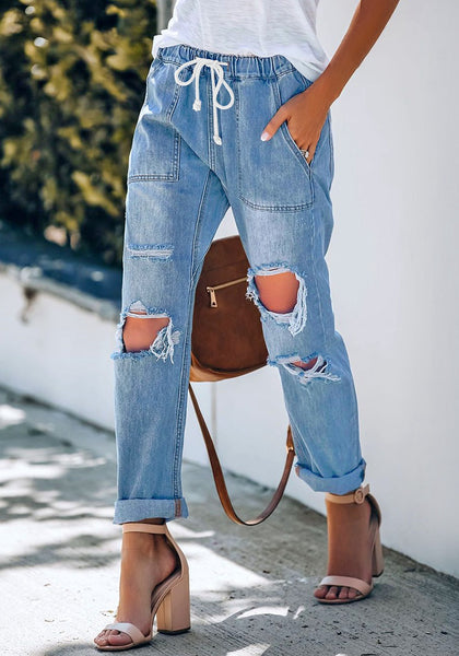 Model poses wearing medium blue drawstring-waist cuffed raw hem ripped boyfriend jeans