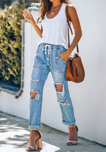 Full body shot of model wearing medium blue drawstring-waist cuffed raw hem ripped boyfriend jeans
