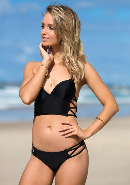 Angled view of model wearing cutout side bikini set - black