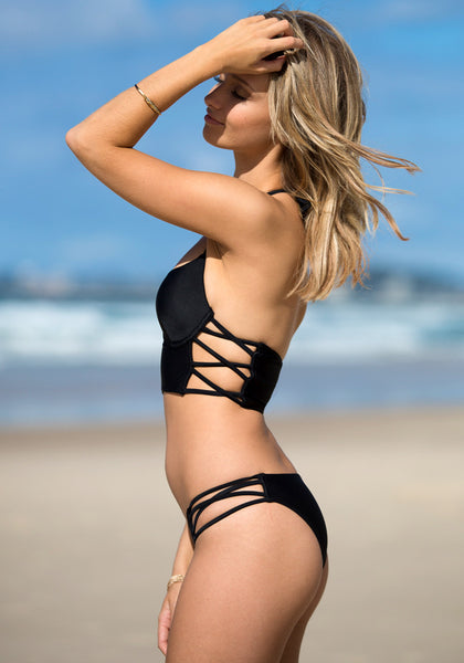 Sexy sideways view of model wearing cutout side bikini set - black