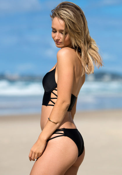 Side view of model in cutout side bikini set - black