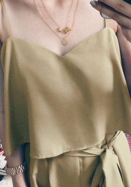 A close-up shot of a woman in cream-colored casual outfit posing while wearing gold coin and stars layered necklace