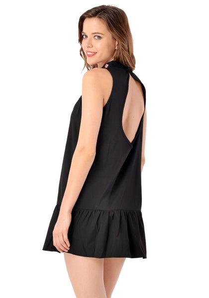 Angled back shot of model in black mock neck floral embroidered dress
