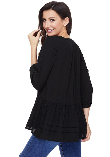 Angled back shot of model wearing black button-front puffed sleeves tunic