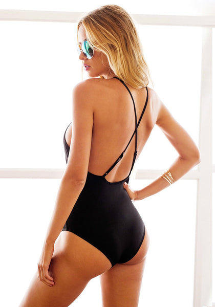 Angled back shot of woman in black lace-up swimsuit