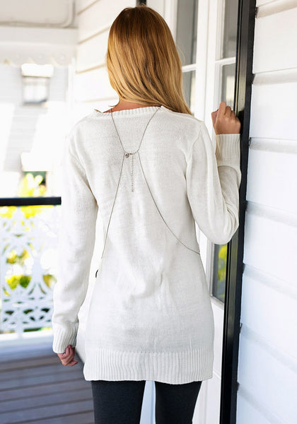 Angled back view of girl in beige side slit tunic sweater
