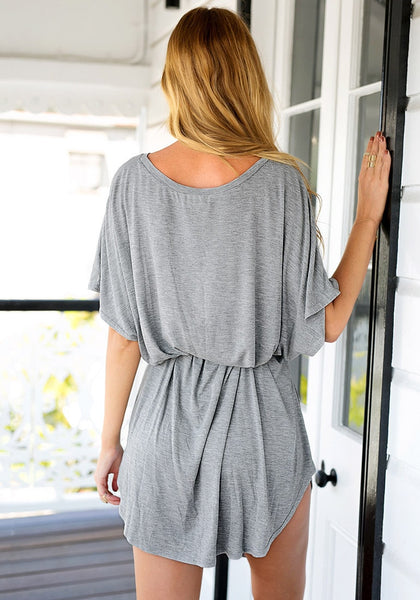 Angled back view of girl in grey t-shirt dress