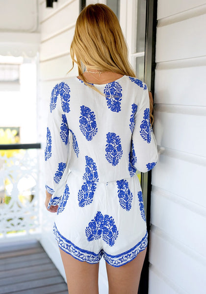Angled back view of girl in trumpet sleeve surplice romper
