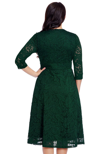 Angled back view of model in plus size green lace surplice midi dress