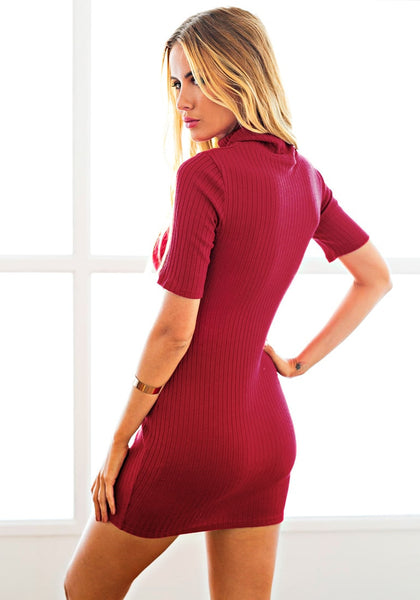 Angled back view of model in red ribbed turtleneck bodycon dress