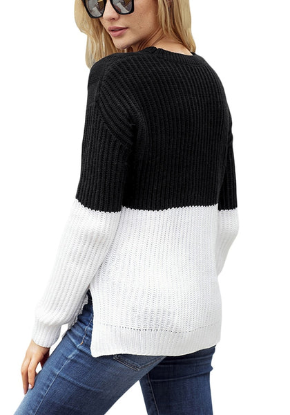 Angled back view of model wearing black and white color block side-slit cable knit sweater