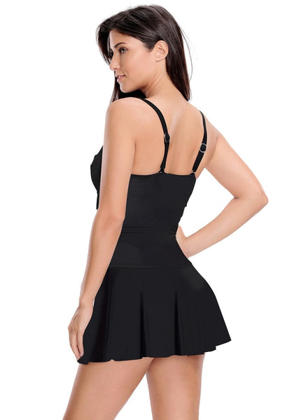 Angled back view of model wearing black ruched pleated swim dress