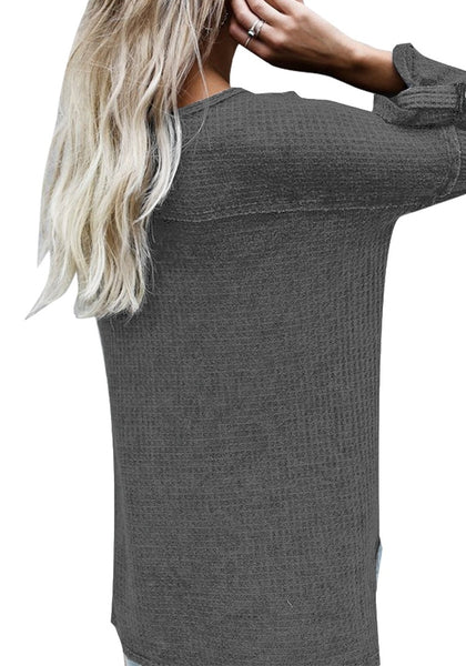 Angled back view of woman in grey front buttons roll-up sleeves textured top
