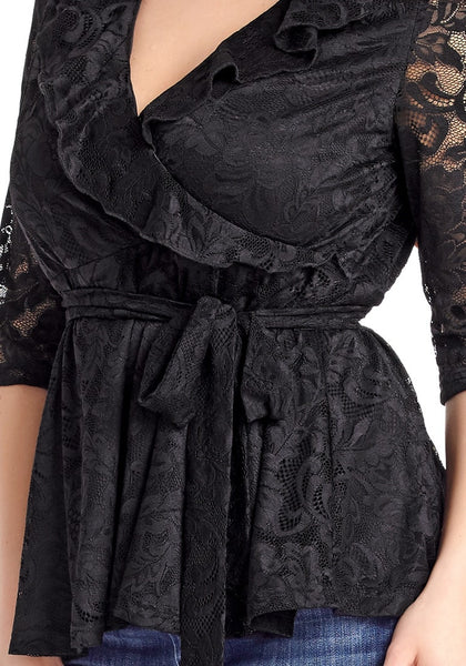 Angled closeup shot of model in plus size black ruffled faux wrap blouse