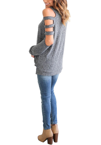 Angled full body shot of woman in grey cold-shoulder hollow-out blouse
