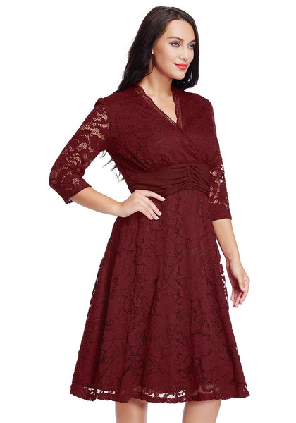 Angled right view of model in plus size burgundy lace surplice ruched-waist dress