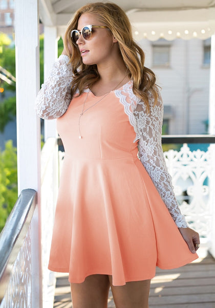 Angled shot of girl in an apricot lace sleeve skater dress