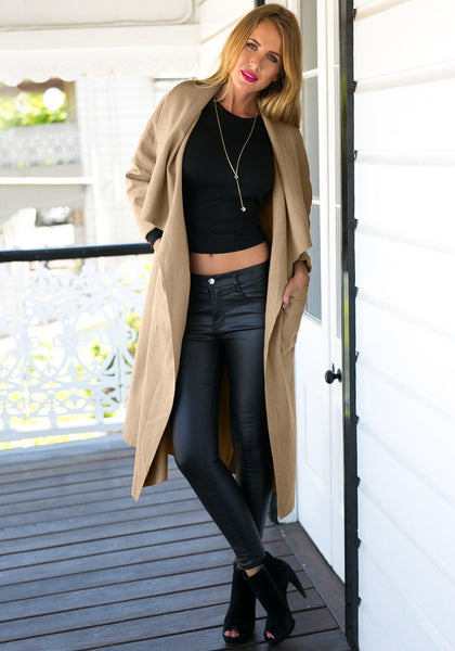 Angled shot of girl in camel draped open-front long coat