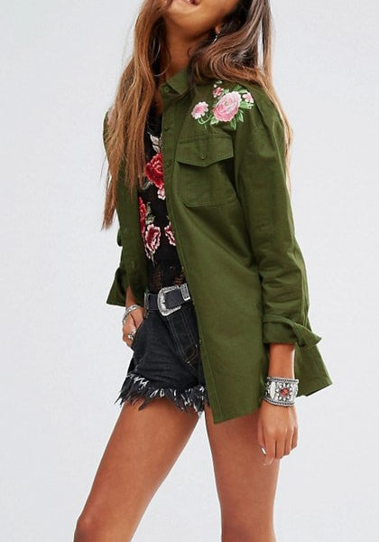Angled shot of model in army green floral-embroidered shoulder shirt