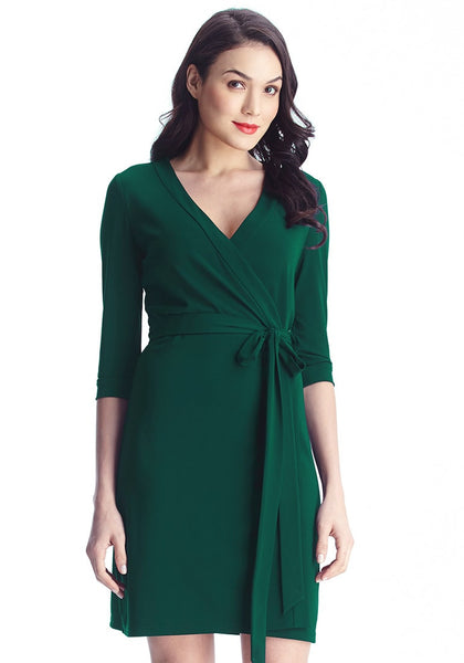 Angled shot of model in green plunge wrap-style belted dress