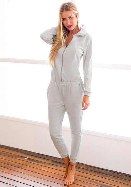 Angled shot of model in grey hooded pajama jumpsuit