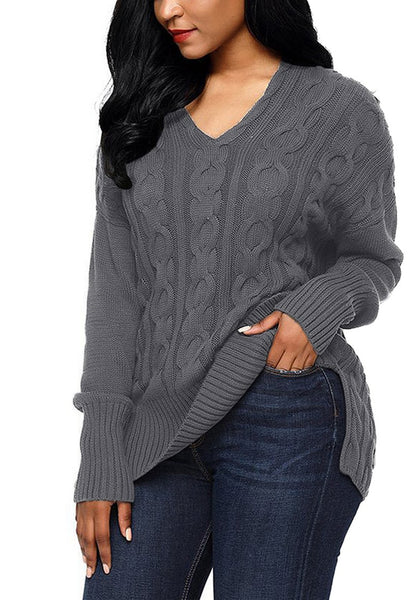 Angled shot of model in grey ribbed cable knit side-slit sweater