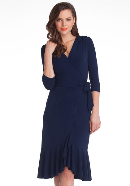 Front shot of woman in navy blue asymmetrical ruffled wrap dress