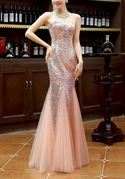 Angled shot of model in peach sequin mermaid evening gown