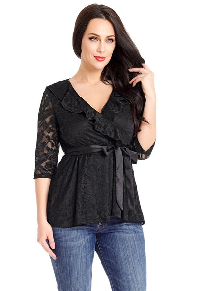 Angled shot of model in plus size black ruffled faux wrap blouse