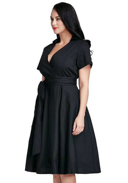Angled shot of model in plus size black surplice midi dress