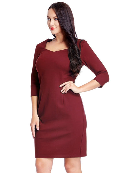 Angled shot of model in plus size burgundy decollete neckline pencil dress