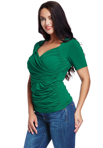 Angled shot of model in plus size green ruched surplice top