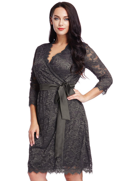Angled shot of model in plus size grey lace crop sleeves wrap dress with one hand at waist