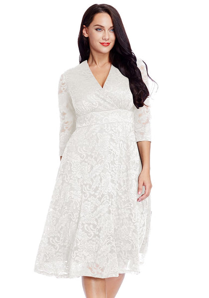 Angled shot of model in plus size white lace surplice midi dress