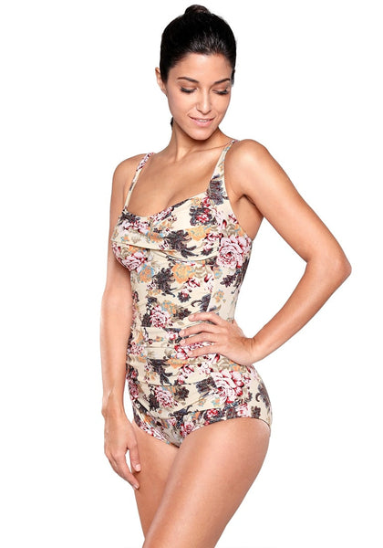 Angled shot of model wearing beige floral-print ruched swimsuit
