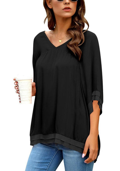 Angled shot of model wearing black V-neck bell sleeves layered loose tunic top
