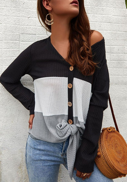 Angled shot of model wearing black V-neckline button-up tie-front colorblock waffle knit top