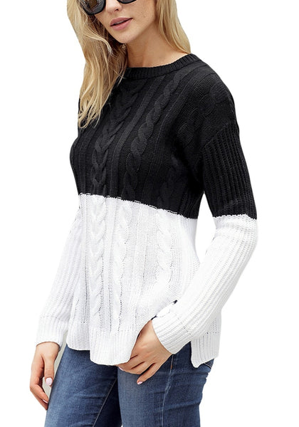 Angled shot of model wearing black and white color block side-slit cable knit sweater