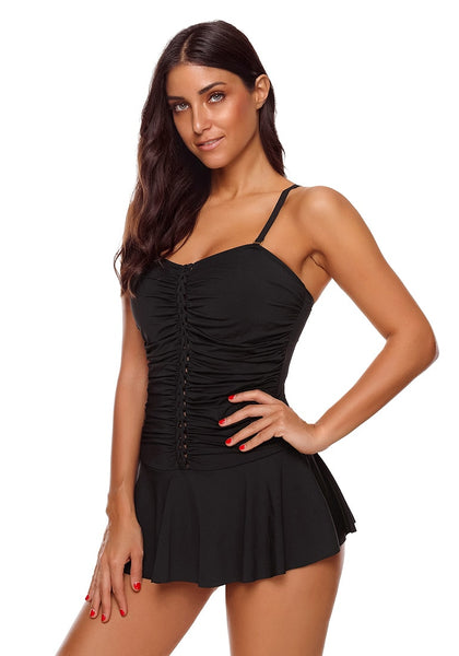 Angled shot of model wearing black braided-front ruched skirted swimsuit